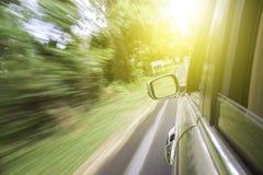 Automobile commovente sulla strada fra la foresta Immagini Stock