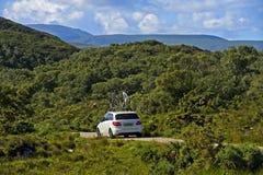 Automobile con uno scaffale della bici su un paese stretto Fotografie Stock