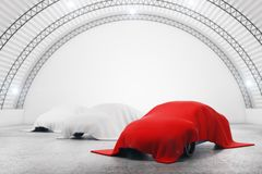 Automobile concept. Abstract warehouse interior with cars under red and white cloths. Automobile concept. 3D Rendering Stock Photography