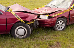 Automobile Crash Closeup. Closeup of two red Automobiles that wrecked with Yellow Do Not Cross Police Tape Royalty Free Stock Photography
