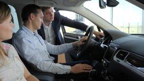 Automobile d'acquisto, giovane coppia, sedentesi nel machina, maschio felice video d archivio