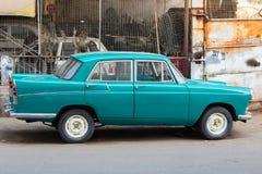 Automobile d'annata parcheggiata fuori di un'officina di riparazione Fotografia Stock