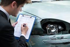 Automobile d'esame dell'agente di assicurazione dopo l'incidente immagini stock libere da diritti