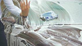Automobile dallo stomaco delicato di lavaggio dell'autista e schiuma fuori dalle mani, servizio stringere dell'autolavaggio video d archivio