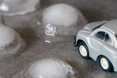Automobile del giocattolo circondata dai cubetti di ghiaccio Guidando per il concetto del maltempo Fotografia Stock Libera da Diritti
