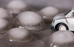 Automobile del giocattolo circondata dai cubetti di ghiaccio Guidando per il concetto del maltempo Immagini Stock Libere da Diritti