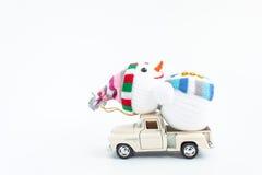 automobile del giocattolo con il pupazzo di neve su bianco Fotografie Stock