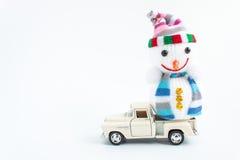 automobile del giocattolo con il pupazzo di neve su bianco Immagini Stock