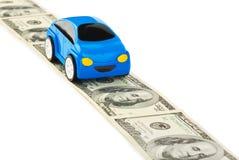 Automobile del giocattolo sulla strada dei soldi Immagine Stock
