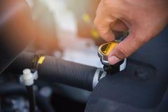 Automobile del radiatore del controllo con la mano sul motore nel centro di servizio dell'automobile fotografia stock