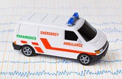 Automobile dell'ambulanza del giocattolo su ecg Immagine Stock