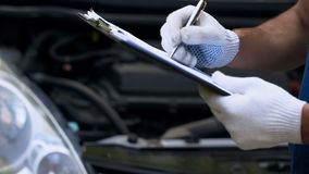 Automobile di diagnosi del meccanico, scrivente i calcoli dei costi, ispezione annuale del veicolo, fine su immagini stock