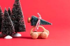 Automobile di legno miniatura che porta un albero di Natale Fotografia Stock Libera da Diritti