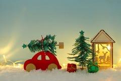 Automobile di legno rossa che porta un albero di Natale sopra neve davanti a fondo blu ed alle luci dorate della ghirlanda fotografia stock libera da diritti