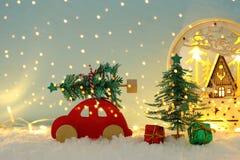 Automobile di legno rossa che porta un albero di Natale sopra neve davanti a fondo blu ed alle luci dorate della ghirlanda fotografia stock