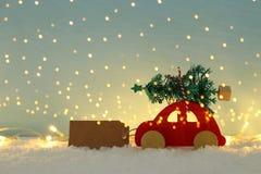 Automobile di legno rossa che porta un albero di Natale sopra neve davanti a fondo blu ed alle luci dorate della ghirlanda fotografie stock libere da diritti