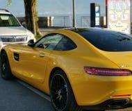 Automobile di lusso dell'oro sopra una luce dell'oro vicino alla riva del lago Lemano immagini stock
