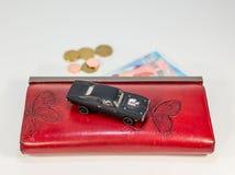 Automobile di lusso sul portafoglio rosso con il giocattolo costoso soldi Fotografia Stock Libera da Diritti