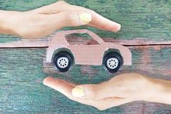 Automobile di modello del cartone con le ruote nere protette dalle mani della donna su fondo di legno rustico fotografia stock