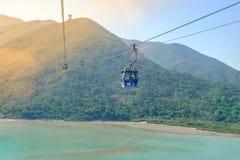 Automobile di Ngong Ping Cable con i turisti sopra il porto, le montagne ed il fondo della città, visitare Tian Tan o il grande B fotografia stock