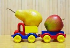 Automobile di plastica del giocattolo con la mela e la pera Fotografia Stock