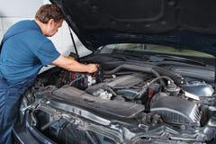 Automobile di prova dell'elettricista con il multimetro al garage immagine stock libera da diritti