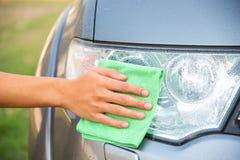 Automobile di pulizia con il panno del microfiber la lucidatura dell'automobile del faro Immagini Stock