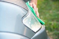 Automobile di pulizia con il panno del microfiber la lucidatura dell'automobile del faro Fotografia Stock