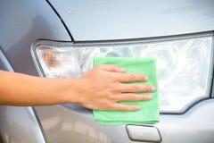 Automobile di pulizia con il panno del microfiber la lucidatura dell'automobile del faro Immagine Stock