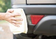 Automobile di pulizia con l'automobile di lucidatura del panno del microfiber la parte posteriore dell'automobile Fotografie Stock