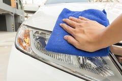Automobile di pulizia dell'uomo facendo uso del panno del microfiber Fotografia Stock Libera da Diritti