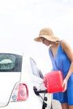 Automobile di rifornimento di carburante della donna contro il chiaro cielo il giorno soleggiato Fotografie Stock