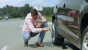 Automobile di sollevamento dell'uomo sulla presa per il cambiamento della gomma piana stock footage