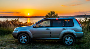 Automobile di Suv al tramonto in natura vicino al lago immagini stock libere da diritti