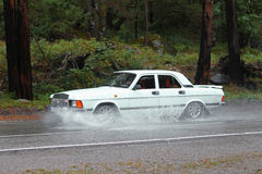 Automobile driving on the puddle on a highway Stock Image