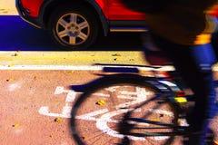 Automobile e bici sui precedenti delle piste ciclabili del segno Immagine Stock