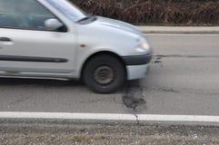 Automobile e buca sulla strada Immagine Stock