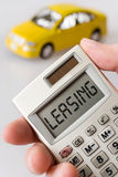 Automobile e mano che tengono una calcolatrice tascabile con il testo di leasing Fotografia Stock Libera da Diritti