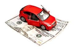 Automobile e soldi del giocattolo sopra bianco Fotografia Stock