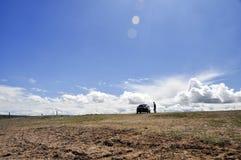 Automobile ed essere umano sotto il cielo blu Fotografia Stock