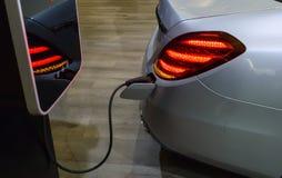 Automobile elettrica con un cavo elettrico inserito alla stazione di carico fotografia stock libera da diritti