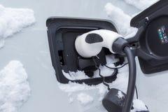 Automobile elettrica di carico nell'orario invernale fotografia stock libera da diritti