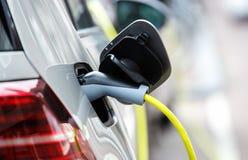 Automobile elettrica moderna che incarica del cavo elettrico immagini stock