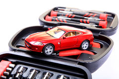 Automobile engineering. Toy car over tool kit against white background Royalty Free Stock Image