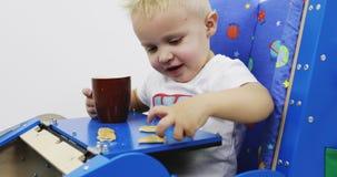 Automobile funzionale del giocattolo con una tavola Il bambino si siede e mangia i biscotti e beve il tè stock footage