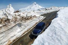 Automobile fuori strada Mitsubishi che guida sulla strada della montagna in tunnel della neve circondato dagli alti cumuli di nev Immagini Stock Libere da Diritti