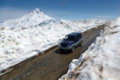 Automobile fuori strada Mitsubishi Pajero iO che guida sulla strada della montagna in tunnel della neve su fondo del vulcano Fotografia Stock