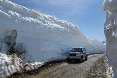 Automobile fuori strada Mitsubishi Pajero iO sulla strada della montagna in tunnel della neve circondato dagli alti cumuli di nev Immagine Stock Libera da Diritti