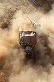Automobile gialla che alimenta su collina ripida, calciando sabbia e polvere Fotografia Stock