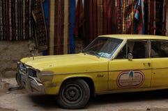 Automobile gialla con sul fondo del tessuto in strada di Aleppo Immagini Stock
